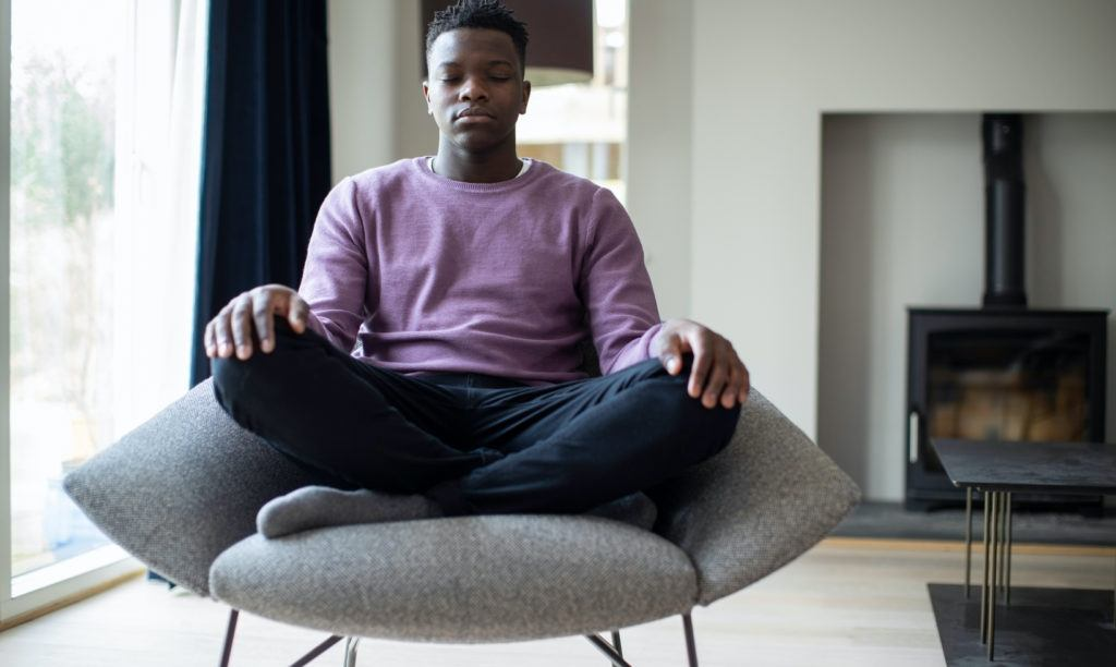 Young man meditating seated in chair